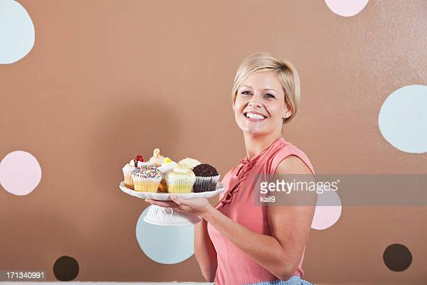 Woman holding plate of cupcakes