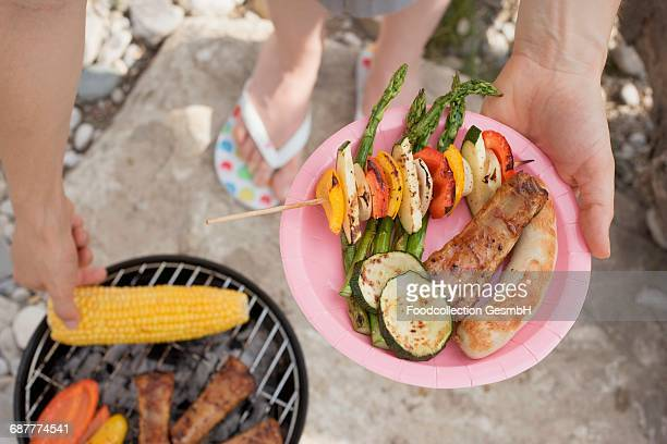 woman holding plate of grilled food at barbecue on river bank - paper plate stock photos and pictures
