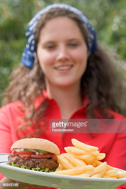 Woman holding plate of hamburger and chips, close up