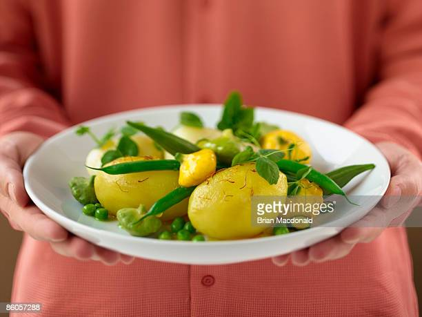 Woman holding plate of summer vegetables