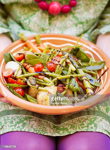 Woman holding plate of vegetable salad