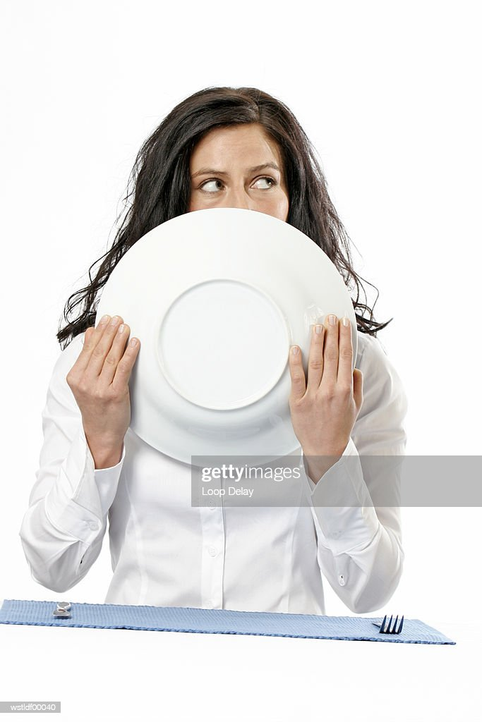 Woman holding plate, partly obscuring face, portrait : Foto de stock