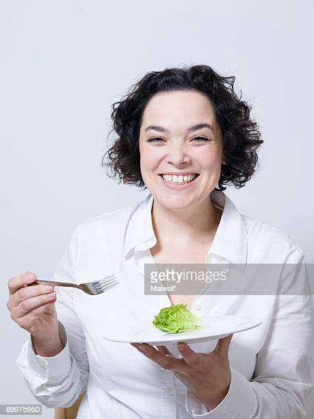 woman holding plate with leaf of salad