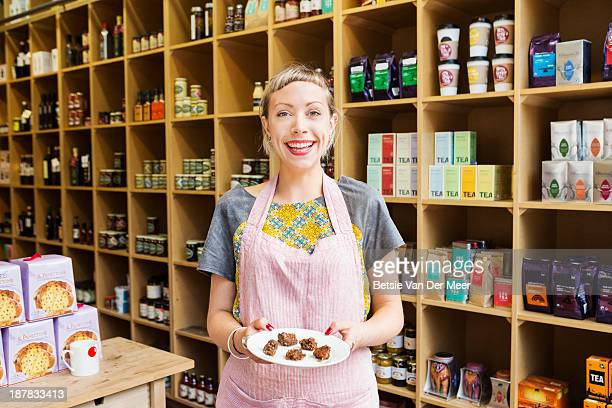 Woman holding  plate with small cake bites in shop