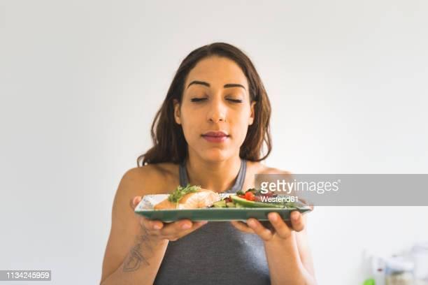 woman holding plate with vegetables and salmon - servierfertig stock-fotos und bilder