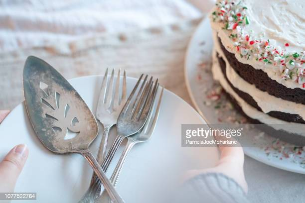 woman holding plates, silverware for serving vegan chocolate christmas cake - hygge stock pictures, royalty-free photos & images