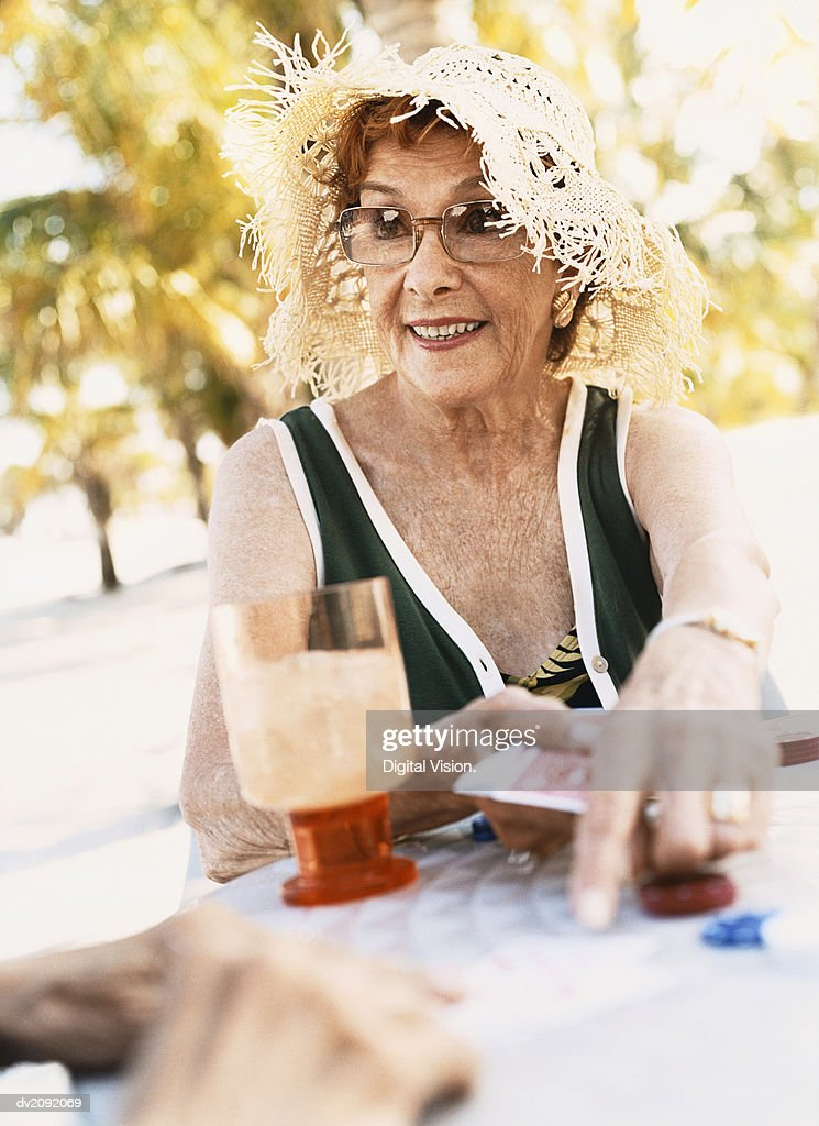 Woman Holding Playing cards and Pointing at a Table : Stock Photo