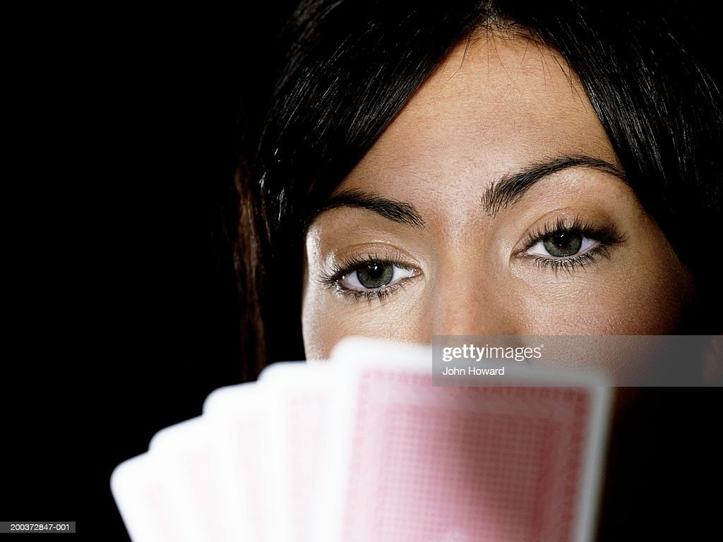 Woman holding playing cards up to face, close-up (focus on woman) : Stock Photo