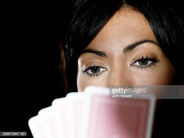 Woman holding playing cards up to face, close-up (focus on woman)