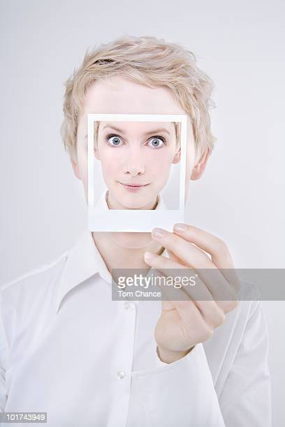 Woman holding polaroid picture in front of her face, close-up