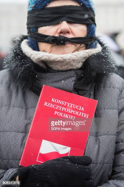 A woman holding polish constitution while using black bands over her eyes and mouth during a silent assembly named Stolen Justice in Krakow Stolen...