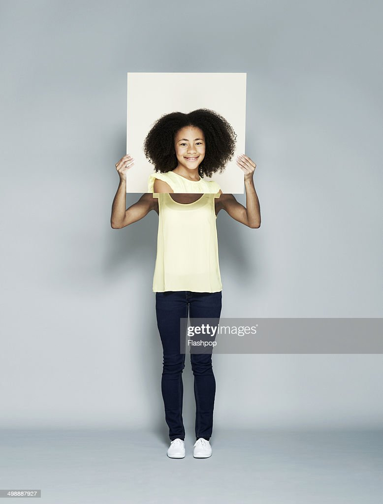 Woman holding portrait of herself as a child : Stock Photo