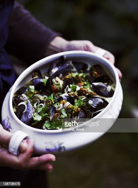 woman holding pot of mussels, close-up - mujeres de mediana edad fotografías e imágenes de stock