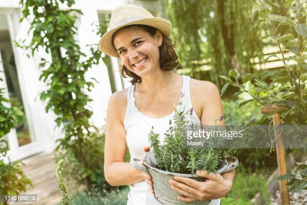 woman holding pot plant - mid adult women stock pictures, royalty-free photos & images