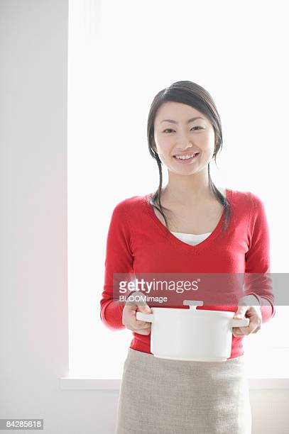 Woman holding pot, smiling