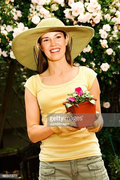 woman holding potted plant - つば広 ストックフォトと画像