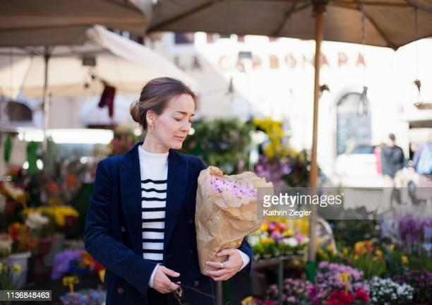 woman holding potted plant that she bought at flower market - opgestoken haar stockfoto's en -beelden