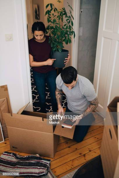 woman holding potted plant while man reading book during unpacking boxes at house - loader reading stock pictures, royalty-free photos & images