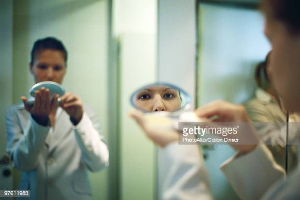Woman holding powder compact putting on makeup, looking at camera in reflection in mirror