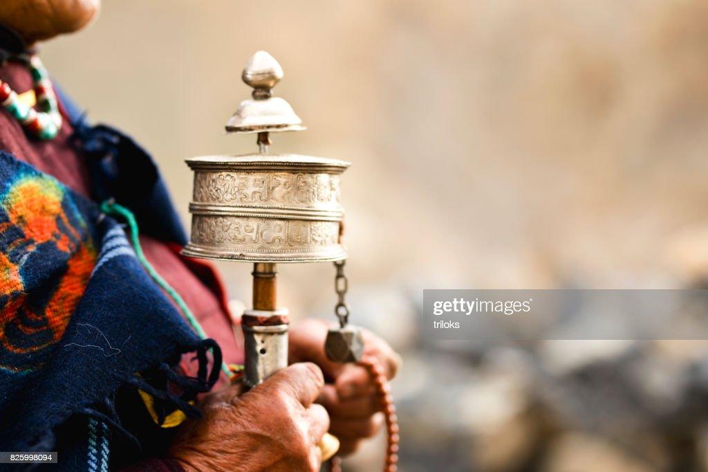 Woman holding prayer wheel and beads : Stock Photo