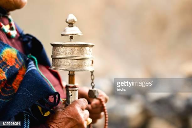 Woman holding prayer wheel and beads