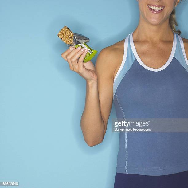 Woman holding protein bar