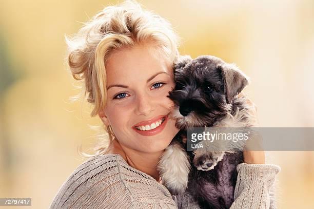 Woman holding puppy against face, portrait