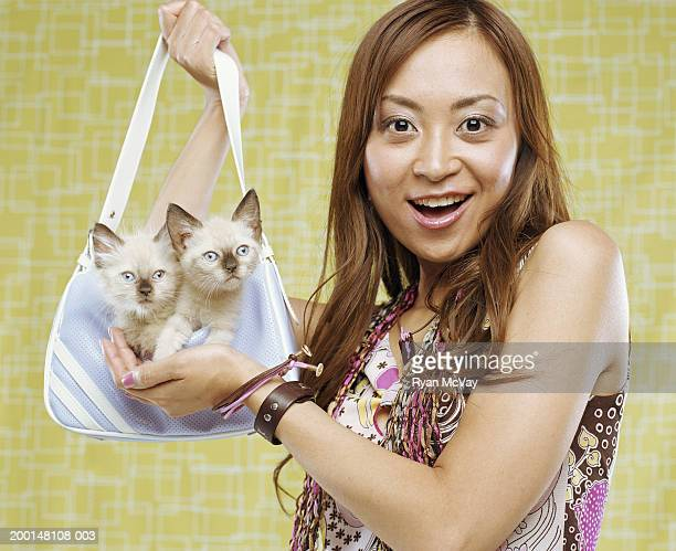 Woman holding purse with Siamese kittens