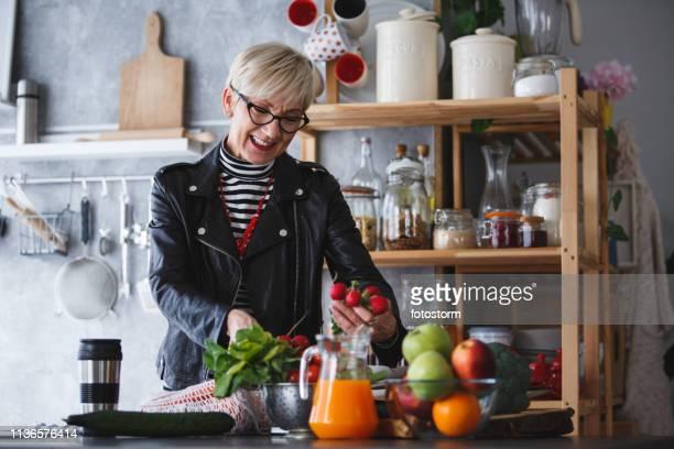 台所で大根を持ち、食料品を開梱する女性 - ベジタリアン料理 ストックフォトと画像