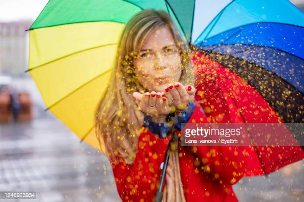 woman holding rainbow color umbrella in a festive mood on a rainy day. blowing glitter confetti - lena spoof stock pictures, royalty-free photos & images
