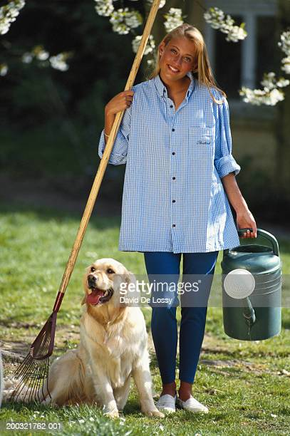 Woman holding rake and watering can in garden