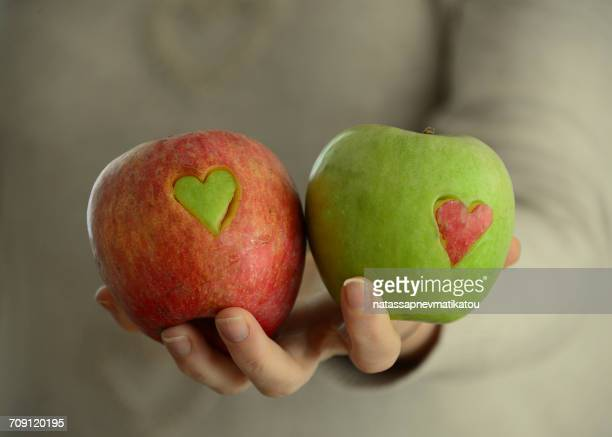 woman holding red and green apples with heart shapes missing - ペア ストックフォトと画像