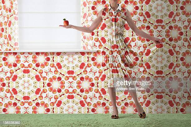 woman holding red apple blends into the wallpaper