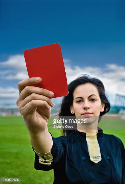 Woman holding red card on soccer pitch