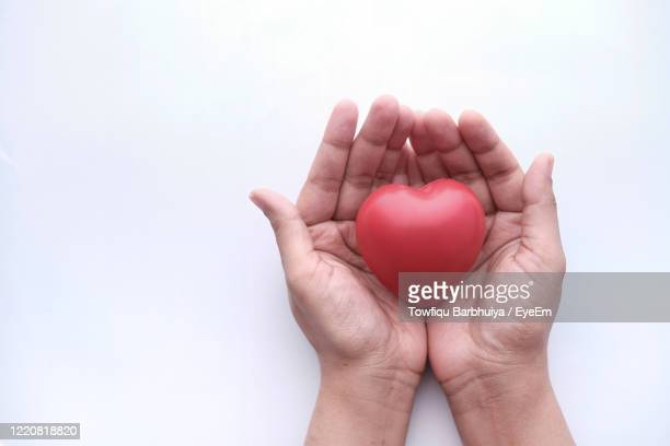 woman holding red heart in hands on wooden table - giving tuesday stock pictures, royalty-free photos & images