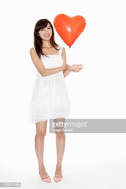 Woman holding red heart shaped balloon, studio shot