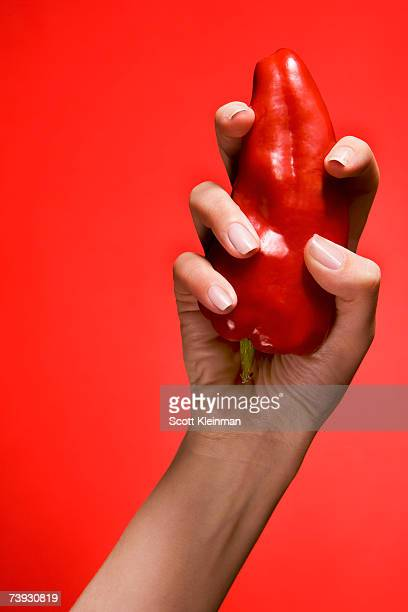 Woman holding red pepper in studio, close-up of hand