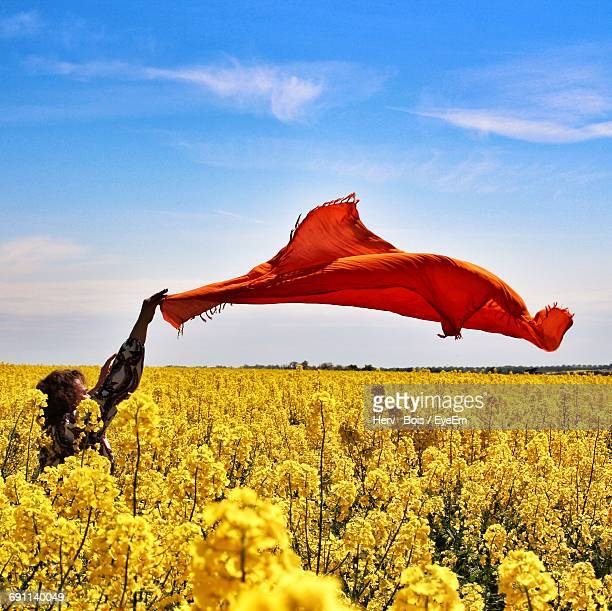 Woman Holding Red Scarf On Oilseed Rape Field