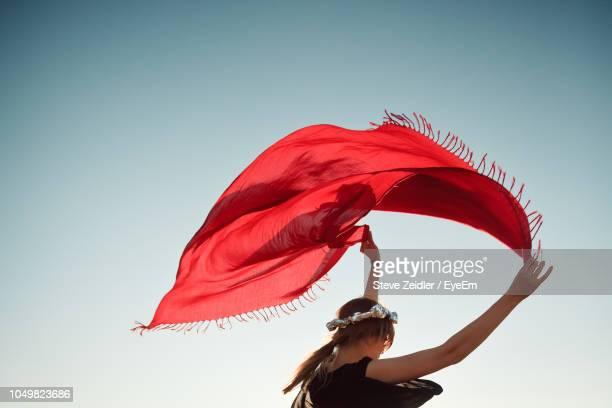 woman holding red scarf while standing against clear sky - echarpe - fotografias e filmes do acervo