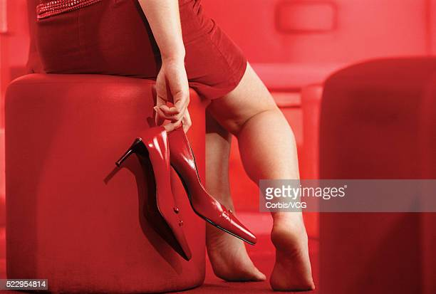 woman holding red shoes - legs and short skirt sitting down stock photos and pictures