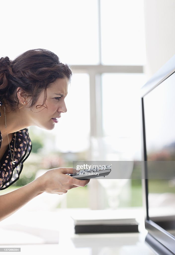 Woman holding remote control to TV and squinting : Stock Photo