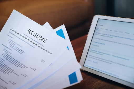 woman holding resume application with using tablet digital to job search on internet. applying for a job concept. 1076968328
