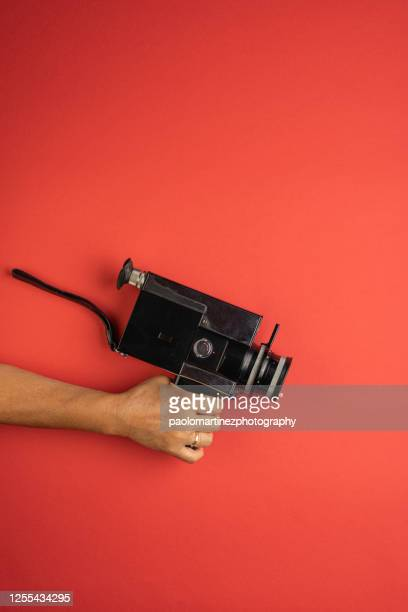 woman holding retro 8mm camera on red background - film director stock pictures, royalty-free photos & images