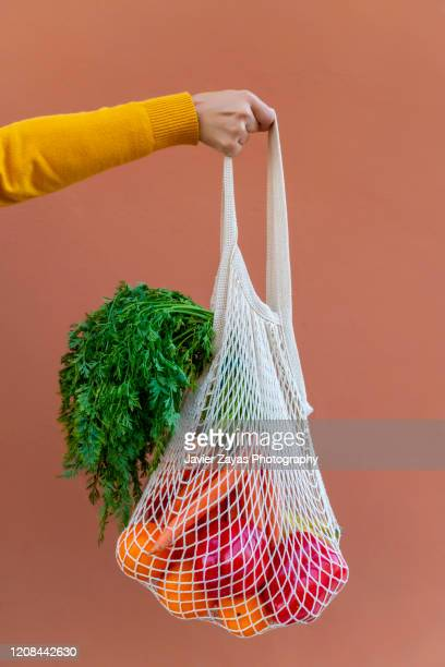 woman holding reusable cotton mesh bag with fruit and vegetables - bolsa objeto fabricado fotografías e imágenes de stock