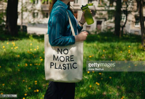 woman holding reusable cotton zero waste bag with text no more plastic. outdoors portrait in sunny day. eco friendly bags concept. - bag stock pictures, royalty-free photos & images