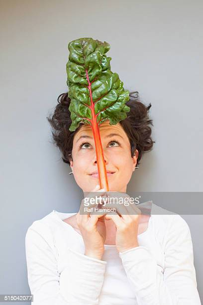 A woman holding rhubarb while looking at it over grey background