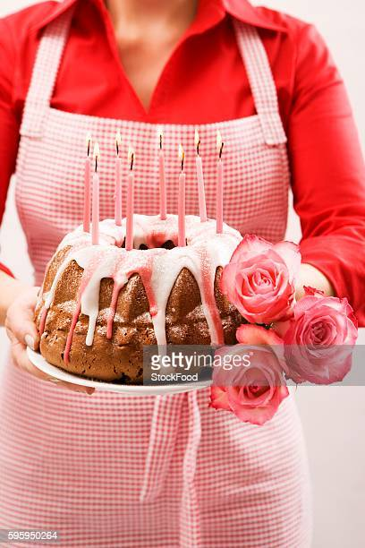Woman holding ring cake and roses for a birthday