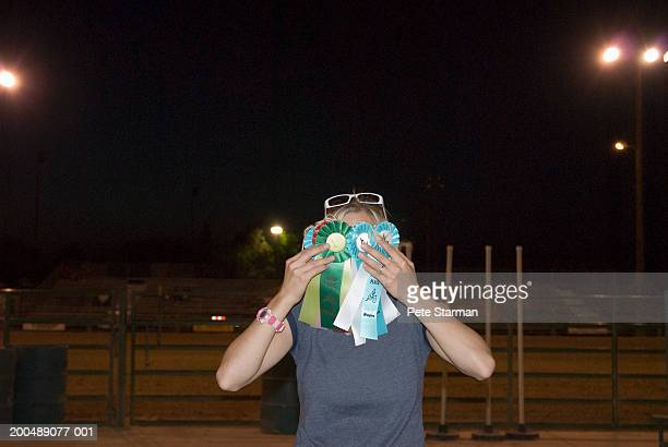 woman holding rosettes in front of face - small group of objects stock pictures, royalty-free photos & images