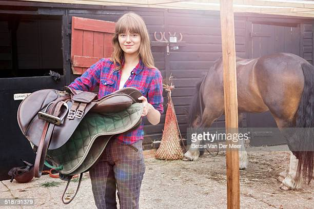 Woman holding saddle, horse eating in background.