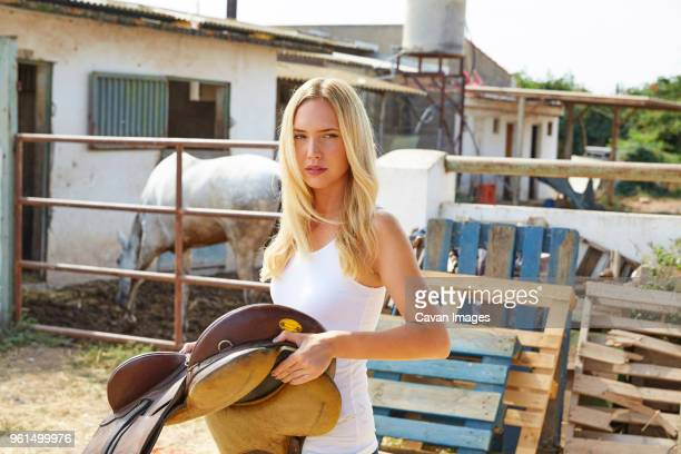woman holding saddle looking away - cowgirl photos et images de collection